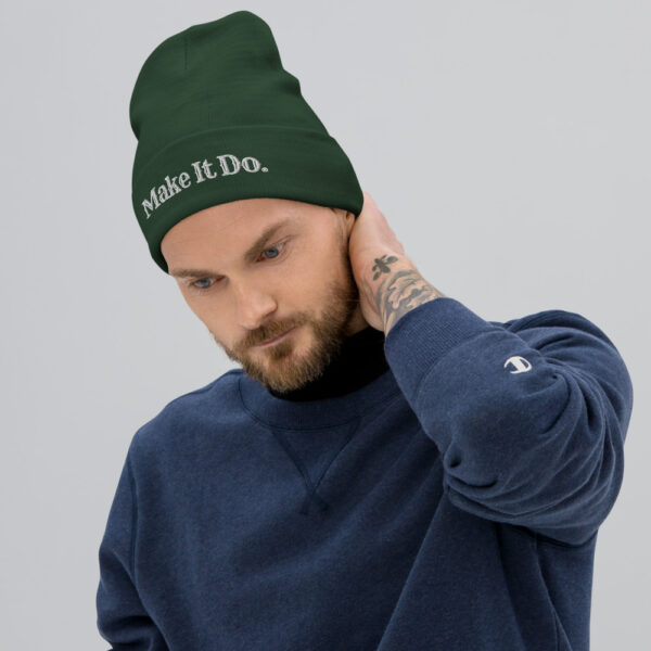 Guy wearing a green beanie from Gifts For Men that has a Make It Do® logo that's embroidered with white stitching.